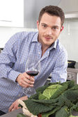 Happy well looking man drinking red wine in the kitchen — Stock Photo