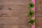 Wooden background with red and white checkered ribbon and green — Stock Photo