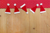 Christmas hats, red and white polka dot fabric - wooden background — Stock Photo