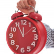 Stock Photo: Symbol of time : hand holding red clock , eleventh hour isolated