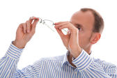 Man holding up his glasses and looking at them isolated on white — Stock Photo