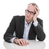 Frustrated businessman wearing glasses sitting at desk — Stock Photo