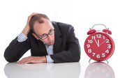 Businessman overworked with red clock isolated on white backgrou — Stock Photo
