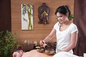 Asian woman making massage to a man — Stock Photo