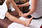 Hands of woman making massage at a man feets — Stock Photo