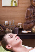 Young woman enjoying massage in salon — Stock Photo