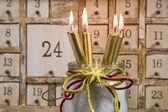 Shabby calendar with burning candles — Stock Photo