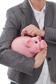 Put coin into piggy bank — Stock Photo
