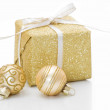 Gold Christmas gift box with bauble decorations isolated on white background — Stock Photo