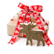 Christmas present in red with a wooden handmade elk or reindeer — Stock Photo