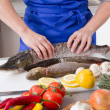 Woman is cooking fresh fish — Stock Photo