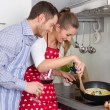 Young couple in love cooking together in the kitchen and have fun — Stock Photo