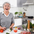 Senior or older woman with grey hair cooking in kitchen — Stock Photo