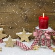 Traditional country style decoration in red for christmas with wooden stars, red candle and a checkered ribbon for a greeting card — Foto Stock #34664259