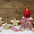 Traditional country style decoration in red for christmas with wooden stars, red candle and a checkered ribbon for a greeting card — Stockfoto