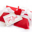 Close up of red present box with German text for christmas with a red heart on a snowy white background — Стоковое фото