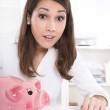 Young pretty business woman count money, coins with a piggy bank — Stock Photo #34664963