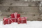 Group of red Christmas presents, with snow on grey wooden background - idea for a greeting card or coupon with a red checkered ribbon — Stock Photo