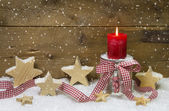 Traditional country style decoration in red for christmas with wooden stars, red candle and a checkered ribbon for a greeting card — Photo