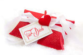 Detailní záběr červené krabičce s německým textem na vánoce s červeným srdcem na sněhově bílém pozadí — Stock fotografie