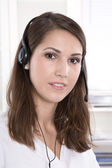Brunette woman at helpdesk wearing headset — Stock Photo