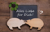 Greeting card with clover and two wooden pigs - like a couple - luck for new years day, valentine's day or birthday - love - on a old rustic chalkboard — Stock Photo