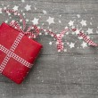 Christmas Present wrapped in red paper on a wooden background for a greeting card — Foto de Stock