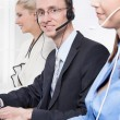 Telesales or helpdesk team - helpful man with headset smiling at desk - man and woman - callcenter — 图库照片
