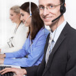Telesales or helpdesk team - helpful man with headset smiling at desk - group woman and man — Stockfoto #35185749