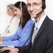 Telesales or helpdesk team - helpful man with headset smiling at desk - group woman and man — Stock Photo