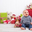 Christmas and birthday - cute baby sitting barefoot and looking  — Stock Photo