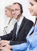 Telesales or helpdesk team - helpful man with headset smiling at desk - man and woman - callcenter — Stock Photo