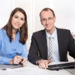Successful teamwork - smiling man and woman in a blue blouse at desk — Stock Photo #35527611