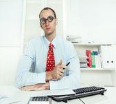 Arrogant man sitting at desk with glasses, a red tie and a blue shirt — Stock Photo