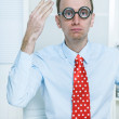 Stunned man with big glasses and a red tie at work like a comedian — Stock Photo #35530623