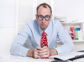 Angry or frustrated young businessman sitting thoughtful at desk — Stock Photo