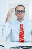 Stunned man with big glasses and a red tie at work like a comedian — Stock Photo