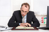 Businessman at desk with problems, stress and overworked sitting — Stock Photo