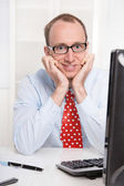 Happy young Business man with glasses and a red tie sitting at desk — Stock Photo