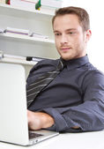 Man in office with laptop — Stock Photo