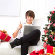 Boy on Christmas Eve with laptop — Stock Photo