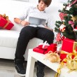 Boy surfs on laptop in Christmas — Stockfoto