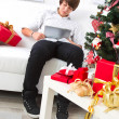 Boy surfs on laptop in Christmas — Stock Photo