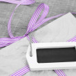 Giftbox with purple striped ribbon — Stock Photo