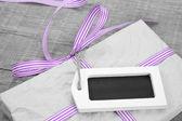 Giftbox with purple striped ribbon — Stock Photo