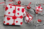 Gift box wrapped in white paper with hearts — Stock Photo