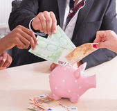 People putting cash in piggy bank — Stock Photo