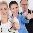 Thumbs up: businessman and two businesswoman - success. — Stockfoto #36236337