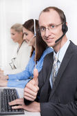 Agent smiling while working on his computer in a call-center. — Stockfoto