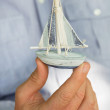 Stock Photo: Man holding a small toy sailing boat - concept for sailing or cruising